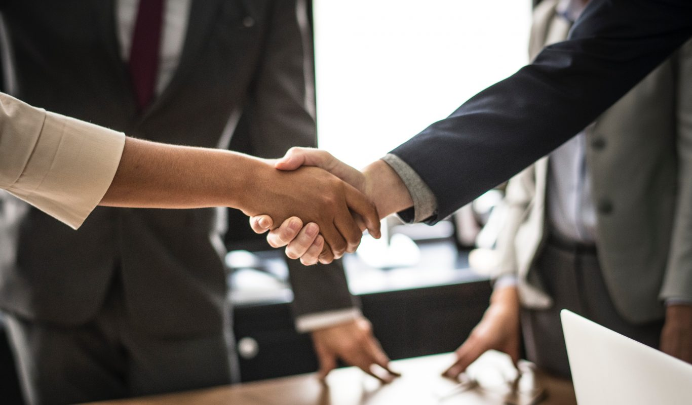 Two people shaking hands on agreement of new mortgage sale